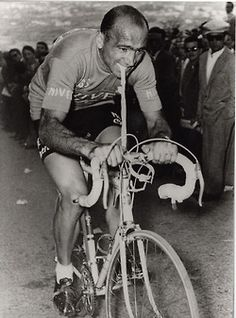 MAGNI PULLING A TUBE! [BROKEN COLLARBONE, 1956 GIRO]  What a badass. To cut some of the pain from bar grip, he ties a tube to them, steers with his jaws, and grinds through the suffering with teeth clenched and will indomitable.