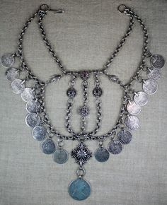 A heavy and elaborate Palestinian 'iznaq' (chin-chain necklace) from Bethlehem. Late-Ottoman era, 18th century. In heavy silver. The small coins are all Spanish 2 Reales from the early 1700s with an earliest date of 1717. In the center there are geometric flower jewels, and a central cross with filigree, leaves, a star, and a flower. The coin at center is a Maria Theresa Thaler.