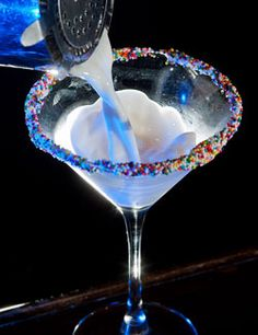 Pinnacle Cake Vodka, Godiva White Chocolate Liqueur, amaretto and cream in a martini glass garnished with rainbow sprinkles on the rim.(rosario, we could make this pink and use pink sprinkles too?)