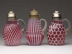 Victorian glass. Cranberry syrup containers. One swirled, one vertical and one honeycomb
