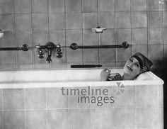 Badeeinrichtungen, eine junge Frau in der Badewanne ullstein bild - ullstein bild/Timeline Images #Badewanne #Baden #Badezimmer #waschen #Hygiene #Badespaß #Bad #historisch #Badehaube #schwarz-weiß #Frau #Badeschwamm