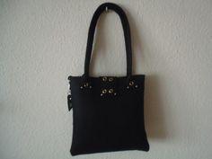 Schwarze Filztasche in kleinerem Format mit Taschenklappe, die mit goldfb. Ösen designt ist. Strasssteinchen und das obligatorische MissMarpleHerz dür