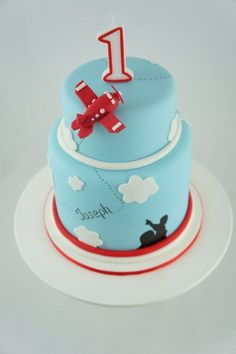 Red Aeroplane cake created by two little figs cakes. Baby blue and white fondant with red detailing, 3 d red aeroplane cake topper and hand painted silhouette.