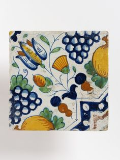 Tile made in the Netherlands ca.1610-1630. Beginning in the 17th century, tilework became a typical feature of the Dutch home. Painted tiles were deployed around fireplaces, on wainscots, along corridors, and around skirtings. This example is painted with polychome fruit and flowers in a style infuenced by Italian majolica. Victoria and Albert Museum object