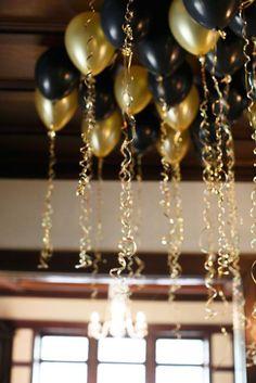 Decoración de bodas en negro y dorado muy sencilla de hacer con globos en ambos colores con cinta en dorado.