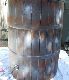 Paint a plastic barrel to look like an expensive wooden one to use for catching rain water