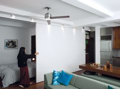 To make the modest space flexible, Robert built a sliding wall with QuietRock soundproofing drywall on the living-room side and rich PureBond walnut-veneer plywood on the bedroom side. Sliding Wall, Sliding Doors, Shelves In Bedroom, Bedroom Wall, Book Shelves, Style At Home, Small Apartments, Small Spaces, Drywall