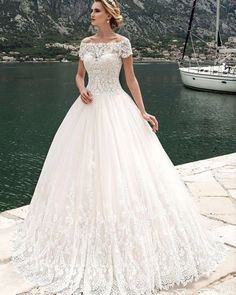 This slightly modest short sleeve wedding gown has an illusion neckline that covers the bust line. The ball gown skirt creates a very traditional looking fashion piece for the bride. You can have custom wedding dress designs like this created with any change and for any shape or size. If a brides dream dress is out of her price range we can also create very similar #replicas of designer wedding dresses that are affordable and much less than the original. get pricing and more details about…