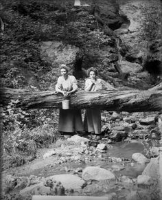 Two women pose behind a log which has fallen across the stream in Parfrey's Glen, Wisconsin, 1909.