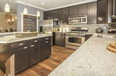 Gray cabinets and a helpful chalk board contrast with wood floors and stainless steel appliances. EnergyStar certified new homes by M/I Homes in Gaithersburg, MD.
