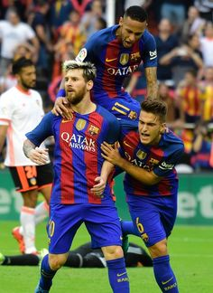 Barcelona's Argentinian forward Lionel Messi (L) celebrates with Barcelona's Brazilian forward Neymar (up) and Barcelona's midfielder Denis Suarez after scoring during the Spanish league football match Valencia CF vs FC Barcelona at the Mestalla stadium in Valencia on October 22, 2016. / AFP / JOSE JORDAN