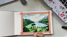 Paint a city by the lake in watercolor in a sketchbook