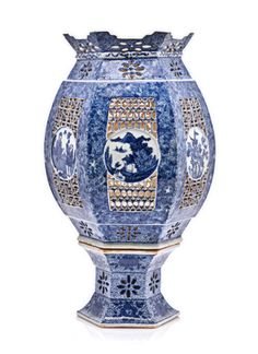 A CHINESE BLUE AND WHITE RETICULATED TABLE LANTERN, EARLY 20TH CENTURY    the hexagonal bulbous body raised on a removable spreading base, each side pierced with a panel of geometric patterns centred by a circular panel depicting figures, flowers and landscapes below a band pierced with flowerheads reserved against a dense flowerhead and foliage ground, the base similarly decorated 40cm high