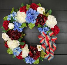 This wreath is defiantly a show stopper!! With its big, bold, fabulous deep ruby red peonies, its lovely white marigolds, expertly arranged along with beautiful blue hydrangeas. This wreath is punctuated by a stunning cascade of red, white and blue linen ribbon. It is truly a