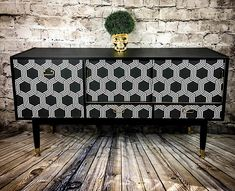 A classic G Plan upcycled sideboard lovingly refinished in a contemporary geometric style. This retro, high end sideboard has been painted a deep black and a monochrome geometric print has been applied on the front, which then received layers of varnish for durability. The