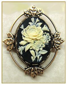 So pretty! I love the black background and the white flower. The edging of metal too is pretty and adds a unique antique look. On a metal chain with maybe a blue ribbon would be so pretty!