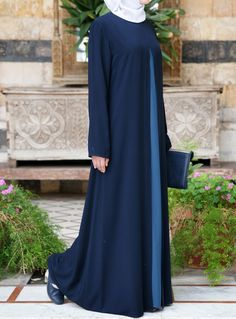 Look effortlessly chic in this simple, yet sophisticated abaya. Pretty and practical, the loose drape is as comfortable as it is modest. Clean lines and a smart contrasting double layered skirt add to the casual and carefree feel. Wear yours with a colorful hijab and fun purse for that perfect pop of personality.