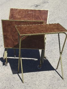 """Set of four vintage TV tables with wood grain print hardboard table tops, brass colored steel legs which fold for storage. This set is in exceptionally clean condition, very nice. The trays measures 21"""" x 15"""", and stand 23 1/2"""" tall when set up."""