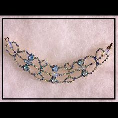 """Vintage Splendor Golden Blue Crystal Lace Bracelet Beautiful Unique Vintage Golden Blue Lace Bracelet - Just a gorgeous unsigned beauty! The detail is superb -  Love the prong set blue gemstones on gold-plated lace style setting and with the added touch of those opaque opalescent baguettes, this bracelet is stunning!  I can easily see it with a pair of jeans during the day and a gorgeous prom/formal dress in the evening. Such a versatile piece! Approximately 7-1/2"""" and great pre-owned…"""