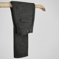 Charcoal-grey wool-tweed proper trousers.
