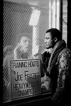 Muhammad Ali, left, taunts Frazier at Frazier's training headquarters in Philadelphia, Pennsylvania, in early 1971. The two men fought for the world heavyweight title on 8 March. Frazier won
