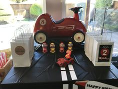 Retro Race Car Theme party - vintage radio rider bike, party favors and car toy for the cake which was not present when this picture was taken.