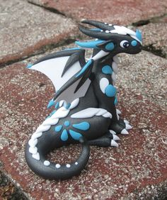 A little slate dragon with white and teal scales handmade from polymer clay! This little 2 and a half inch tall critter is looking for a home in my Mini Mythical Monster shop on Etsy!