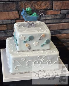 2 Tiered Baby Shower Cake. This two tiered baby shower cake is iced with a light blue fondant and decorated with chocolate rattles and safety pins. Has a topper we made a chocolate baby carriage. We finished the cake with a pearl shimmer. http://www.alittlecake.com/category/baby-shower-cakes/