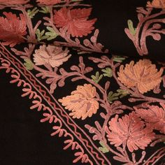 Lustrous mercerised cotton embroidery adorns this fine wool shawl from the mountains of Kashmir, India. The floral pattern covers the shawl giving...