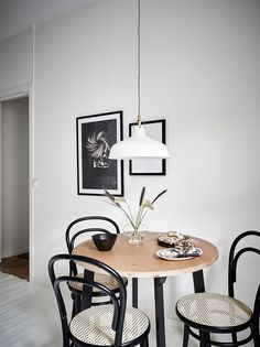 Black Thonet bentwood and cane cafe chairs at a small round kitchen table in a white Striking Monochrome Kitchen in A Warm Gothenburg Apartment Small Round Kitchen Table, Farmhouse Kitchen Tables, Small Tables, Kitchen Chairs, Dining Room Chairs, Round Table With Chairs, Ikea Round Table, Small Dining Area, Farmhouse Small