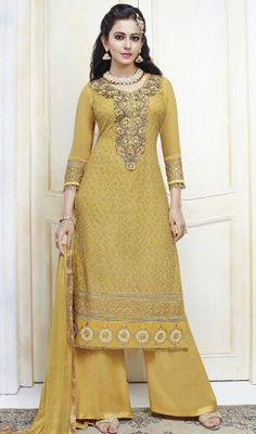 Unfold the aura of freshness with this yellow shade chiffon embroidered palazzo suit showing a effect of sensuality. The attractive lace, resham and stones work through the dress is awe-inspiring. #YellowEmbroideredPalazzoDress