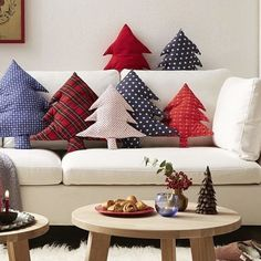 These Christmas Tree Shaped Pillows are so adorable! All it takes are two pieces of festive fabric cut into a pine tree. Then you put the right sides together and sew the seams, leaving a small hole for the stuffing. Turn the fabric tree inside out and start stuffing the cotton in. Seal it with a straight stitch and get ready to make more! Get more decorative Christmas pillow ideas from our linkbio. Image by dawanda.com