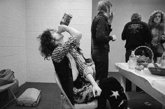 Jimmy Page drinking whiskey while other Led Zeppelin members eat and smoke before a concert. By Neal Preston, 1970s.
