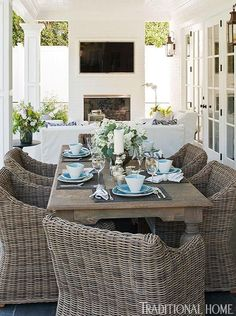 A fireplace with TV, white slipcovered seating, wicker dining chairs all make for a great place to hang out on the porch....V