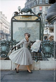 The model is at the Paris Louvre Metro Station wearing a gray Christian Dior dress. captured by legendary photographer Mark Shaw for LIFE Magazine in 1957. by nita