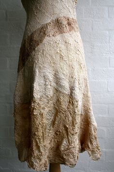 This is an adorable dress with delicious golden caramel tones and fantastic textured organic shaped lines running over the surface. Both front and back have V shaped necklines, the back being smaller and with two toned silks contrasting. A beautiful example of wearable art, totally unique and one of a kind, just like you. The outside layer is silk, with a fine layer of merino wool on the inside that has been nuno felted in a sculptural way to create the dress. All has been hand dyed using…