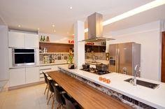 A ilha generosa projetada por Luli Andrade tem pia, cooktop, espaço para refeições e ainda esconde o pilar estrutural.