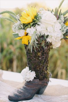 Rustic floral arrangement in a boot. Floral Design: Designs By Laurel ---> http://www.weddingchicks.com/2014/06/04/country-burlap-and-lace-wedding/