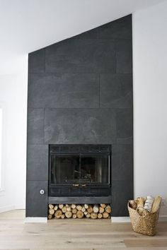a gorgeous, minimalistic floor to ceiling fireplace using oversized black porcelain tile!