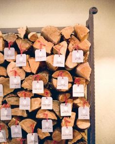 Firewood Escort Card Display - Escort cards bearing crests with the bride's and groom's initials were nailed to a stack of firewood for a winter wedding in Colorado.
