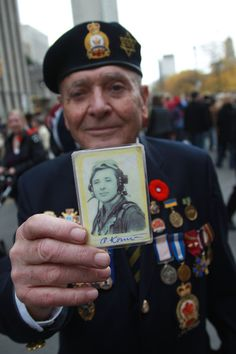 RENE JOHNSTON - RCAF member Armin Konn shows a photo of himself from the past after the Remembrance Day Service at the Old City Hall Cenotaph at 60 Queen Street West. #TorontoStar #photography