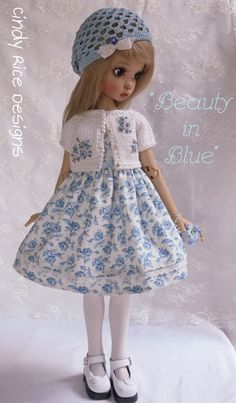 """""""Beauty in Blue"""", a hand made ensemble for Kaye Wiggs BJDs, cindyricedesigns.com .  7-pce. set:  hand knit and embroidered cardigan sweater, crocheted cap, floral print dress, and accessories."""