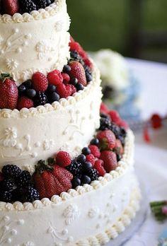 Buttercreme-frosted Hochzeitstorte mit frischen Beeren dekoriert