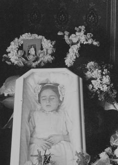 Memento mori of little girl in casket w/ photo of her in bettet days in center of wreath on left-hand side of pic in background.