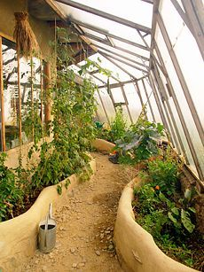 A greenhouse right up against the side of the cob house. That would be so wonderful! --- This is made by Simon Dale (the man who built the Hobbit House)