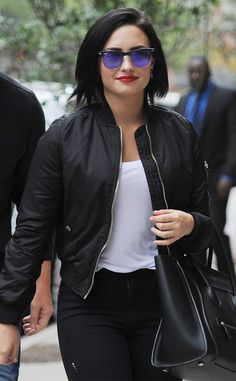 Flaunting jet black tresses, a vibrant red lip and modernized Clubmasters with purple flash lenses, Demi Lovato couldn't have looked more badass!