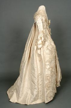 Wedding Dress. 18th century (1758). Cream silk. Shrewsbury Museums Service Worn by the mother of William Hazledine, Shrewsbury Ironmaster.