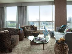 The furnishings for this contemporary living area were chosen to complement the spectacular city view. Aqua draperies frame the floor-to-ceiling windows, while textural elements such as the shag area rug, ceramic cockatoos, woven bronze side table and velvet damask pillows add interest.