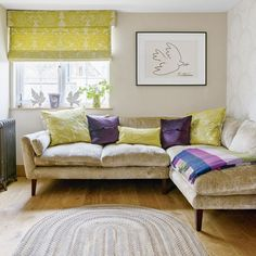 Create a snug corner in a contemporary, modern living room with an L-shaped neutral-coloured sofa and an inviting collection of cushions in lime and purple.