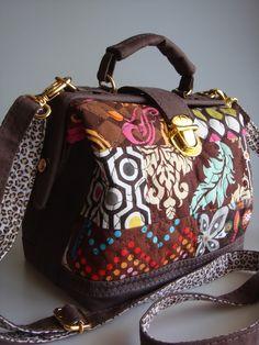 Bolsa feita de lona stone, na frete patchwork de tecido de algodão importado, quitada em manta acrílica. Possui alça de mão e alça transversal. R$ 105,00
